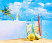 Two glasses of cocktail with lime slice on blur beach and palm — Stock Photo