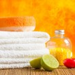 Spa massage border background with towel stacked,red candle and lime — Stock Photo #49937939