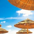 Beach umbrellas on blue sky background with clouds — Stock Photo #51118021