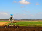 Agriculture Ploughed field with irrigation equipment — Stock Photo