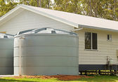 Rainwater conservation tanks on new house — Stock Photo