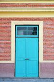 青い木製ドア、レンガの壁 — ストック写真