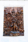 Thai art of wood carving craft on stone wall in Thai temple — Stock Photo