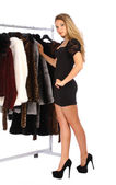 Attractive young woman choosing a fur coat from the hanger — Stock Photo