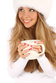 Attractive girl in white fur hat with white mug — Stock Photo