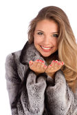 Attractive smiling woman in a gray coat with open hands palm for product — Stock Photo