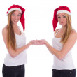 Two twin sisters in Santa hats — Stock Photo