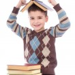 Smiling young boy with a book on his head over white background — Stock Photo #35308309