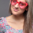 Blonde happy teenage girl with heart sunglasses — Stock Photo