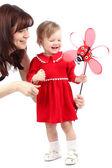 Mutter und mädchen in einem roten kleid, das spielen mit spielzeug isoliert auf weiss — Stockfoto