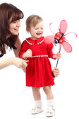 Mother and little girl in a red dress playing with toy isolated on white — Stock Photo