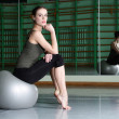 Woman sitting with exercise ball — Stock Photo