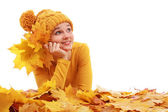 Girl laying in colored autumn leaves — Stock Photo
