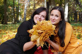 Two young girls sitting in autumn forest — Stock Photo
