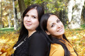 Two young girls sitting in autumn forest — Stockfoto