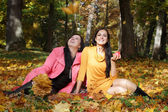 Two young girls sitting in autumn forest — Photo
