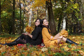 Two young girls sitting in autumn forest — 图库照片
