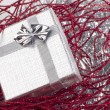 Small christmas gift in red christmas decorations — Stock Photo