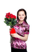 Woman with a bouquet of red roses and heart-shape gift — Stock Photo