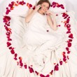 Stock Photo: Womlieing in bed covered by Flower Petals