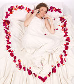 Woman lieing in bed covered by Flower Petals — Stock Photo