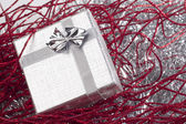 Small christmas gift in red christmas decorations — Foto de Stock