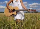 Woman playing guitar on the field — Stock Photo