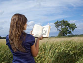 Young girl reading on grass over blue sky — Stock Photo