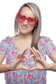 Pretty young woman with heart-shape sunglasses making heart sign — Stockfoto