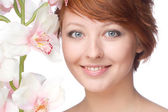 Beauty face of the young beautiful woman with flower — Stock Photo