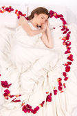 Attractive woman sleeping in bed with roses petals — Stock Photo