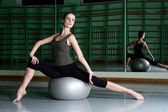 Woman sitting with exercise ball at dance hall — Stock Photo