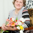 An elderly woman with a bouquet of flowers — Stock Photo