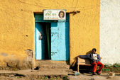 Gonder ethiopia east africa man relaxing outside colourful barbe — Stock Photo