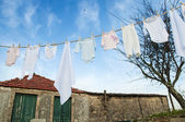 Baby clothes on line outside in rural garden — Stock Photo