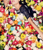 Fashion model posing with flowers — Stock Photo