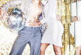 70s disco style couple posing with mirror ball — Stock Photo