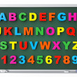 Alphabet Toy magnetic letters over blackboard — Stock Photo #26140323