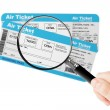 Airline boarding pass tickets with magnifier glass in hand — Stock Photo #45553569