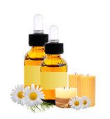 Botellas con aceite de esencia, velas y chamomiles aislados en whi — Foto de Stock