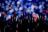 Slavnostní osvětlení a lidi ruce na noční hudební koncert — Stock fotografie