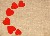 Border frame of red hearts on sack canvas burlap background text — Stockfoto
