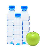 Blue bottles with water and green apple isolated on white — Stock Photo