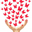 Paper yellow butterflies fly from woman hands over white backgro — Stock Photo