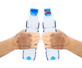 Human hands holding bottles of water isolated on white — Stock Photo
