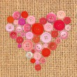 Red buttons heart on sack canvas burlap background texture — Stock Photo #44028391