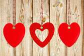 Three red hearts on the wooden weathered rustic background — Stock Photo
