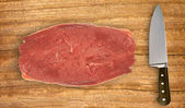 Knife and uncooked meat on cutting board isolated on white — Stock Photo