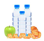 Blue bottles with water, measure tape and green apple isolated o — Stock Photo