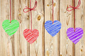 Painted hearts hanging on the wooden weathered rustic background — Stock Photo